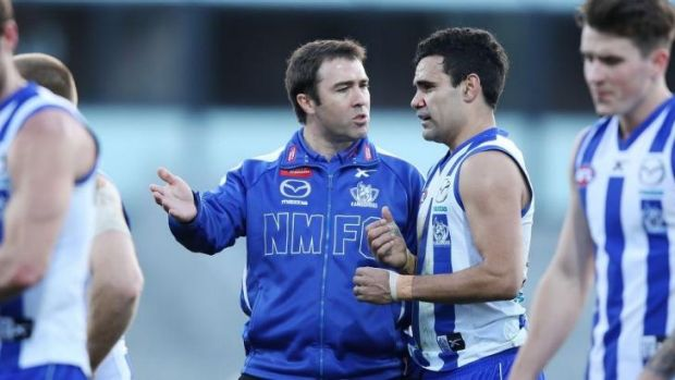 North Melbourne coach Brad Scott has a word with Lindsay Thomas at half-time.