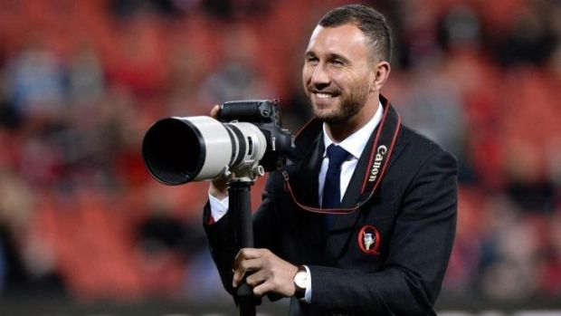 Paparazzi: Injured Reds five-eighth Quade Cooper grabs a camera to take a few pre-game snaps of his teammates.