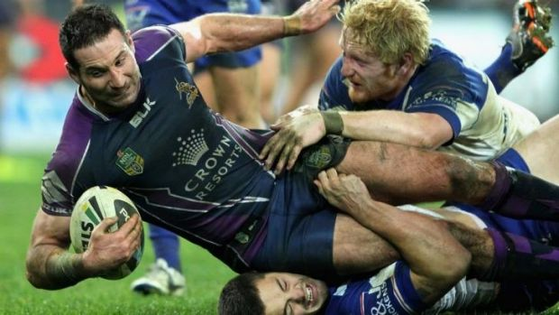 On a tight leash: Bulldogs defenders drag down Storm prop Bryan Norrie.