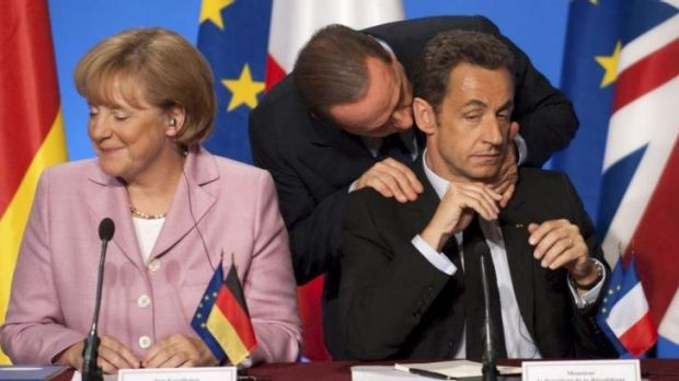 Silvio Berlusconi of Italy has a word in Nicolas Sarkozy's ear during a meeting of European leaders in Paris to discuss ...