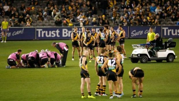Richmond players huddle together as teammate Reece Conca is helped by medical staff after a collision with Port's ...