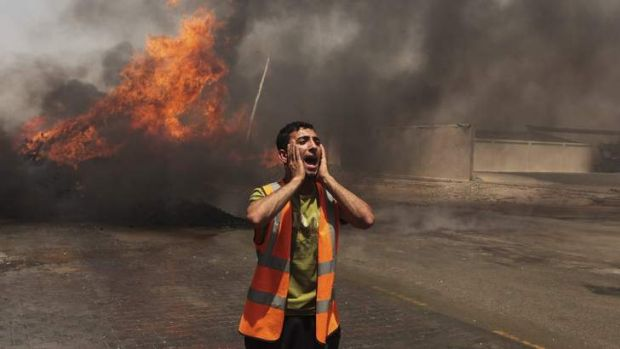 A Palestinian calls for fire-fighters in an industrial area in the east of Gaza City.