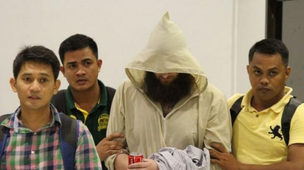 Musa Cerantonio escorted by Philippine immigration officers at Manila airport after his arrest.