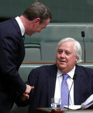 Palmer United Party leader Clive Palmer shakes hands with leader of the house Christopher Pyne after speaking on the ...