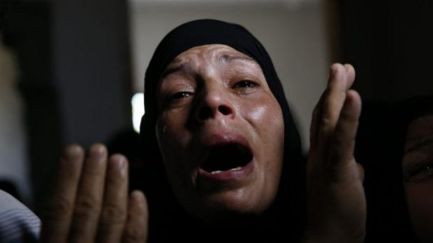 A Palestinian mourner cries at the funeral procession of Mousa Abu Muamer, 56, and his son Saddam, 27, who were killed ...