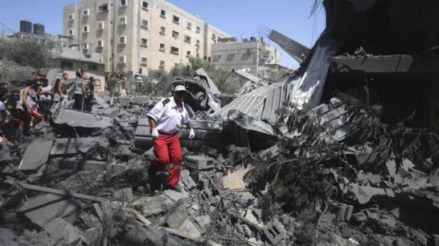 A Palestinian medic walks through the debris of a house that police said was destroyed in an Israeli air strike in Rafah ...