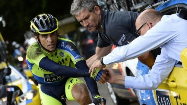 Spain's Alberto Contador gets assistance as he rides after a fall during the 161.50-km tenth stage.
