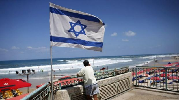 A man looks at the sea as an Israeli flag flutters nearby in Tel Aviv.
