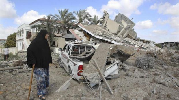 A Palestinian woman walks past the remains of a house which police said was destroyed in an Israeli air strike in Gaza ...