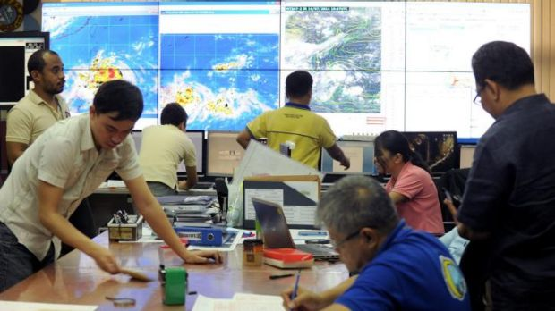 Meteorologists monitor the movement of typhoon Rammasun at the Philippine Atmospheric, Geophysical and Astronomical ...