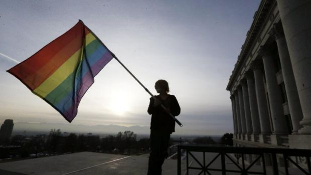 A supporter of gay marriage waves a rainbow flag outside the Utah State Capitol.