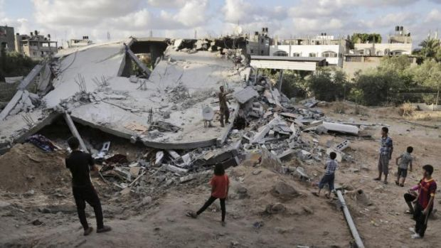 Palestinians look at the rubble of a building destroyed by an Israeli air strike in the northern Gaza Strip town of Beit ...