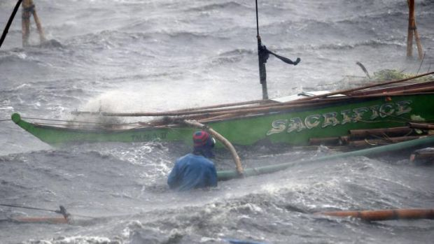 A fisherman tries to secure his boat at Imus.