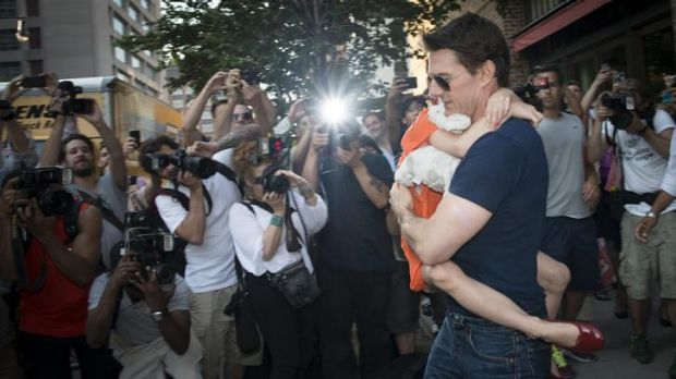 Tom Cruise carries Suri past a group of paparazzi outside his New York apartment.