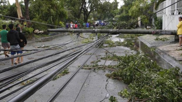 Electric cables lie on a road after its pole fell in Paranaque, Manila.