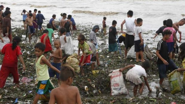 Residents gather salvageable items amidst debris after the onslaught of Typhoon Rammasun along the seashore of the ...