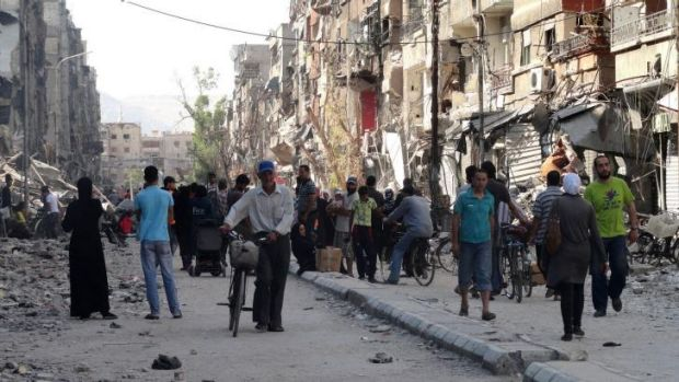 Residents of Yarmuk Palestinian refugee camp, south of Damascus, collect aid on July 7.