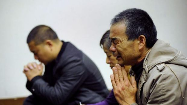 Relatives of MH370 passengers from the flight pray before a meeting in Beijing in March.