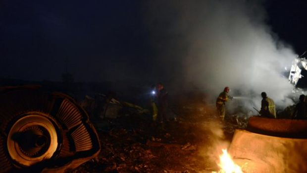 Firefighters extinguish blaze in the MH17 wreckage.