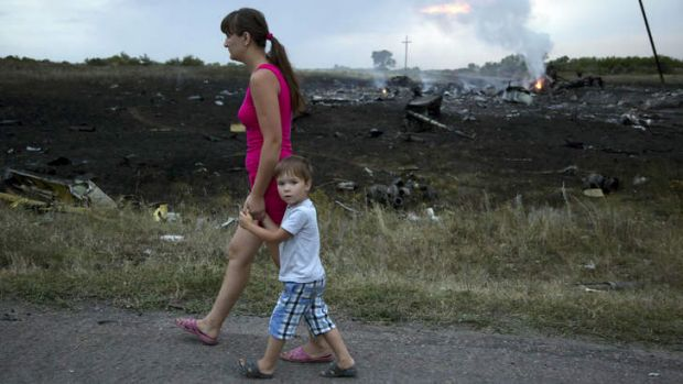 A woman and child walk past the crash site.