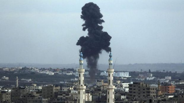 Smoke rises behind a mosque's minarets after an Israeli missile strike in Gaza City.