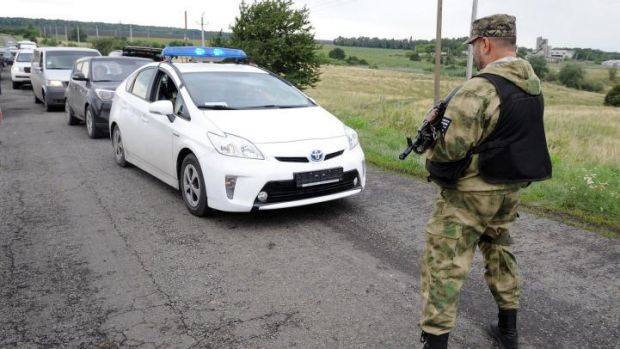 Rebel-held territory ... A man wearing military fatigue stops traffic near the site of the crash site of MH17.