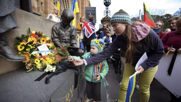 Ukrainian Community placing a reef of flowers and black ribbons at the Mary MacKillop Memorial, St Mary Cathedral in ...
