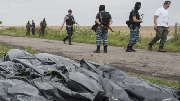 Pro-Russian fighters walk on a road with victims' bodies lying in bags by the side at the crash site of a Malaysia ...