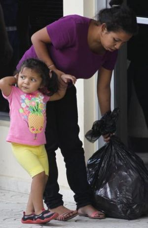 A woman holds her daughter's hand after being deported from the US at the international airport in San Pedro Sula, ...