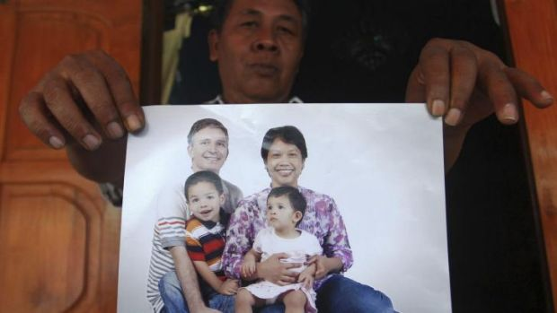 Widi Yuwono, the brother of Yuli Hastini, right, shows her sister's family portrait with her Dutch husband John ...