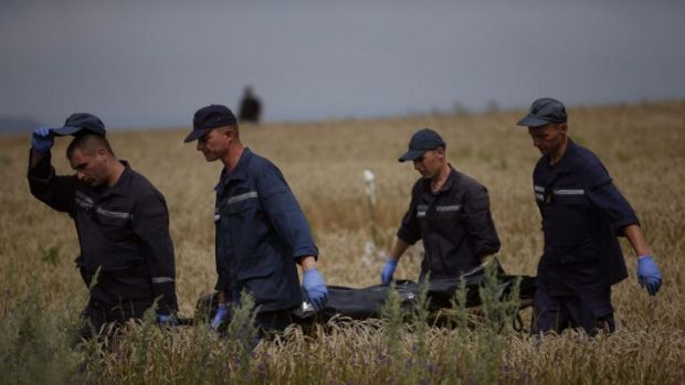Members of the Ukrainian Emergency Ministry carry a body at the crash site of Malaysia Airlines Flight MH17 on Saturday.