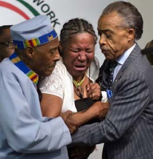 Grief: Eric Garner's wife breaks down during a rally at the National Action Network headquarters.