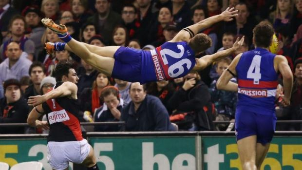 Lachlan Hunter of the Bulldogs leaps for a mark across Essendon's Michael Hibberd at Etihad Stadium on Sunday.