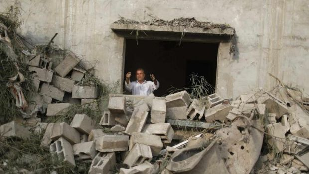 A Palestinian man looks out at a house hit in an Israeli air strike.