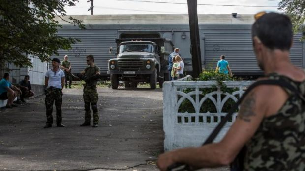 The bodies of victims of the crash of Malaysia Airlines flight MH17 arrive at the Torez train station in the back of a ...