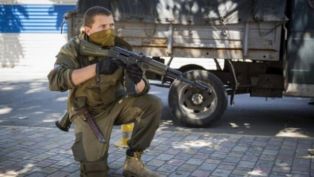 A pro-Russia rebel guards a checkpoint close to the central railway station in Donetsk, Ukraine where fighting has flared up.