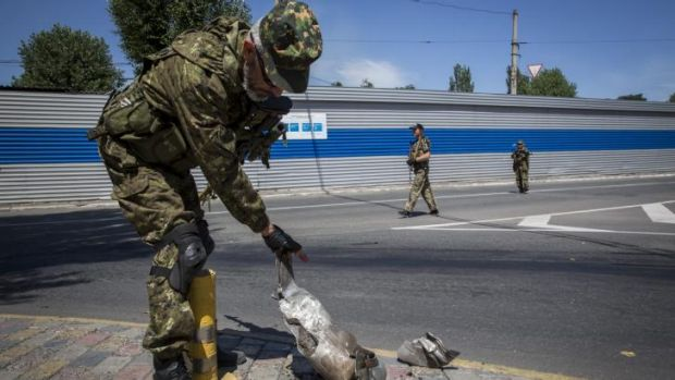 A pro-Russia rebel inspects a Grad rocket that fell in a residential area close to the central railway station in ...