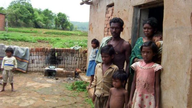 Pusanidevi Manjhi, pictured with husband Gooda and their children, was accused of being a witch by a landowner in ...
