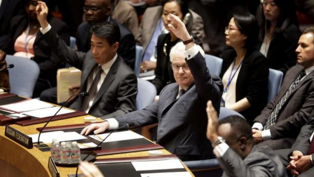 Members of the security council, including Russian Ambassador to the United Nations Vitaly Churkin, centre, vote in ...