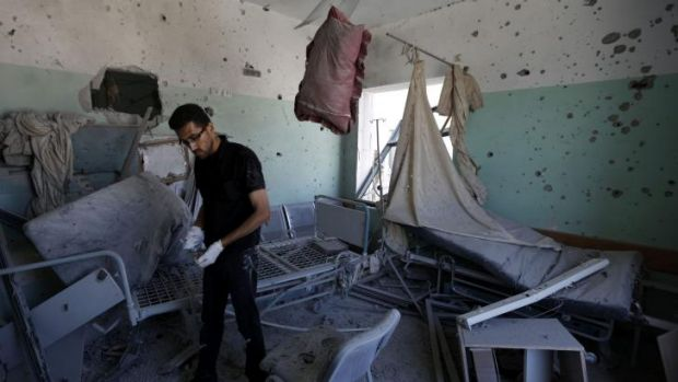 A Palestinian employee inspects damages at the al-Aqsa hospital in which five people died.
