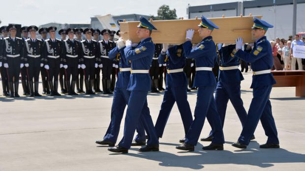Ukrainian soldiers carry a coffin of one of the MH17 victims on to a military plane at Kharkiv airport.