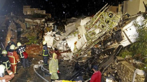 Rescue workers work next to the wreckage of TransAsia Airways flight GE222.