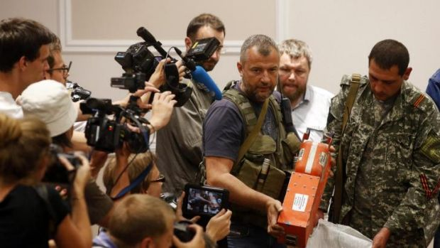 A pro-Russian separatist shows members of the media a black box belonging to Malaysia Airlines flight MH17, before its ...