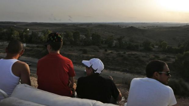 Israelis sit on a sofa on a hill at the Israeli town of Sderot, overlooking the Gaza Strip, as they watch smoke rising ...