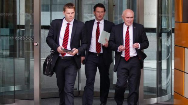 Essendon Chief Marketing Officer Justin Rodski, Chief Operating Officer  Xavier Campbell and Chairman Paul Little walk ...