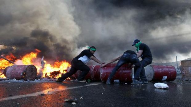 Palestinian protesters block Route 60, the main Jewish settler road in the West Bank.