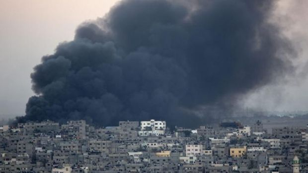 Smoke billows from a building hit by an Israeli air strike in Gaza City on July 25.