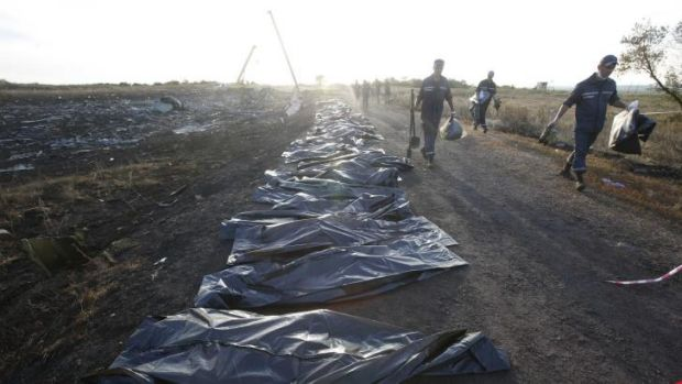 Body bags rest unguarded by the side of a road near the MH17 crash site.