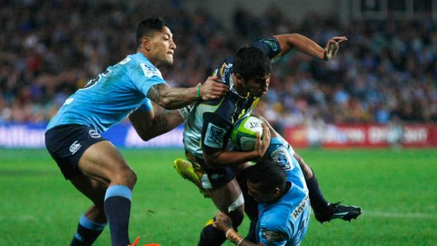 Jarrad Butler tries to make a break for the Brumbies but is tackled by the Waratahs defence.