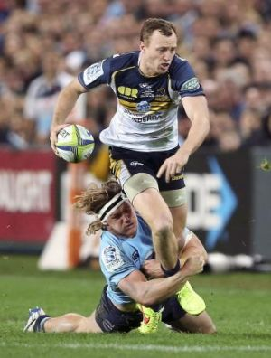 Great tackle: Michael Hooper brings Brumbies fullback Jesse Mogg down.